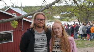 Simon Strömsund och Ida Törnroos med människor och strand i bakgrunden