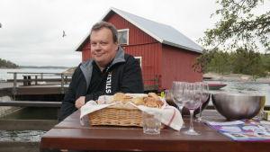 Tom Hildén sitter vid ett bord i stranden på Gullkrona, framför sig har han ett fat med örfilar
