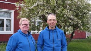 Värdparet i Gullkrona gästhamn står framför boningshuset och ett blommande träd