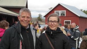 Alf och Joanna Norkko står på stranden på Gullkrona med folk i bakgrunden