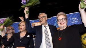 Henna Virkkunen, Petri Sarvamaa och Sirpa Pietikäinen jublar med blommor i händerna.