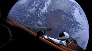 En röd Tesla med en astronautdocka som chaufför sköts upp i rymden år 2018. Här med blått jordklot i bakgrunden