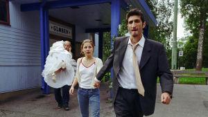Huvudpersonerna i filmen Jalla! Jalla! kommer ut ur ett hus. Till höger en man som bär en tjej i brudklänning över axeln.