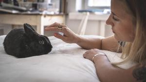Cecilia Ebbe ligger på sängen och krafsar den svarta kaninen Leopold.
