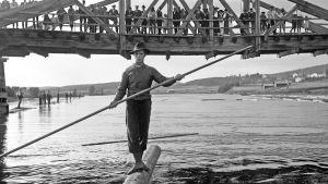 Mies tukin päällä joella, mustavalkoinen kuva