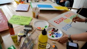Ett bord med målfärger och penslar och pride skyltar