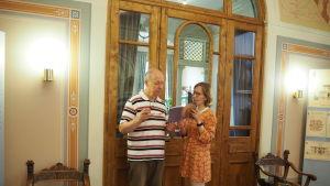 man och kvinna står och tittar i bok framför en stor gammal glasdörr