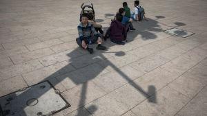 Kinesiska turister vilar ut vid Himmelska fridens torg i skuggan av ett torn av övervakningskameror.