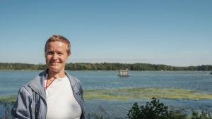 Nainen hymyilee kuvassa etualalla, takana näkyy meri ja pieni harmaa kelluva rakennus.
