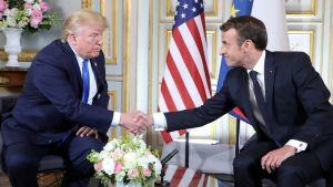 Trump skakar hand med Macron framför en amerikansk flagga.