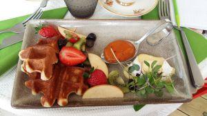 En tallrik med våfflor, brieost, marmelad och bitar av frukt.