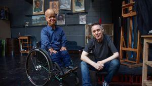 Lyhytkasvuinen mies istuu pyörätuolissa, vieressä jonkinlaisen korokkeen päällä istuu toinen mies. Molemmat katsovat kameraan ja hymyilevät.