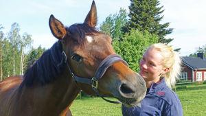 Ryttaren Patricia Westman står ute på en grön äng med hästen Hip.