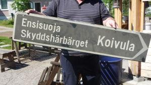 En man håller i en skylt som pekar till höger. På skylten står Skyddshärbärget Koivula.