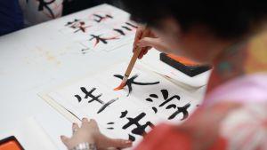 Henkilö kirjoittaa siveltimellä japanilaista kalligrafiaa.