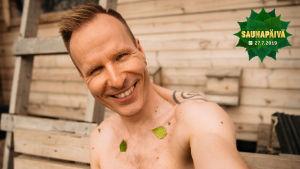 Mikko Kekäläinen koivunlehtiä ihossaan näyttää, että hän osallistuu Saunapäivä-kampanjaan