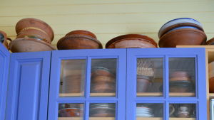 Ett klarblått köksskåp fullt med keramik.