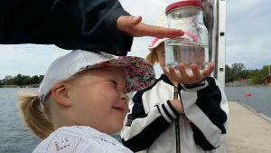 Nellie Walldén, en flicka med vit keps och vit bomullströja, tittar noga på ett vattenprov i en glasburk som hennes syster håller upp.