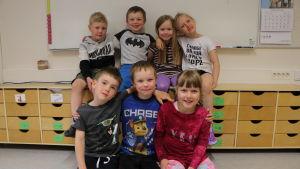 Sju små dagisbarn sitter brevid varandra i daghemmet och håller armarna om varandra. De ler och tittar in i kameran.