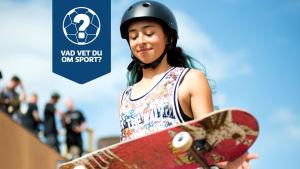 En åkare håller i en skateboard.