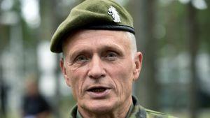 Timo Kivinen står i en grön skog. Han har en grön basker och jackan är kamouflagemönstrad.