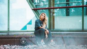 Vaaleahiuksinen laulaja Evelina istuu kivetyksen reunalla ja katsoo suoraan kameraan kädet sylissään. Taustalla isot toimistorakennuksen ikkunat.