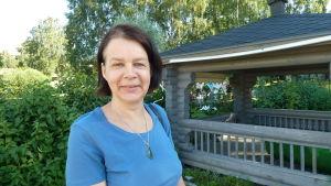 En kvinna står utomhus, framför ett litet tak av trä. Hon har en neutral min. Det är soligt.