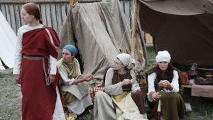 Fyra vikingakvinnor i vikingaby på vikingafestival i Finland.