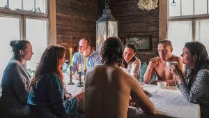 Ihmisiä pöydän ääressä saunan jälkeen vanhassa tuvassa.