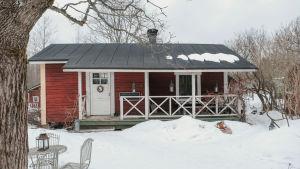 Punainen, hirsinen saunarakennus talvisessa maisemassa.