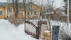 Portti, jonka vieressä kyltti 'Kaurilan sauna', taustalla näkyy keltainen puurakennus.
