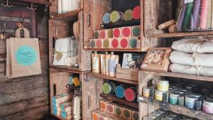 Kosmetiikkatuotteita, kynttilöitä, pellavapyyhkeitä ja muita saunatuotteita hyllyssä myytävänä.