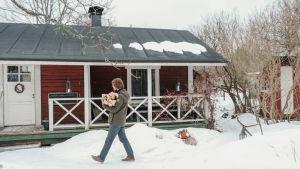 Mies kantaa sylissään halkoja talvella, punaiselle hirsirakennus taustallaan.