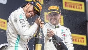 Lewis Hamilton och Valtteri Bottas sprutar champagne på varandra.