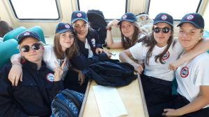 Ett gäng tjejer som sitter med keps i en båt på väg hem från SNU:s läger i Frankrike.