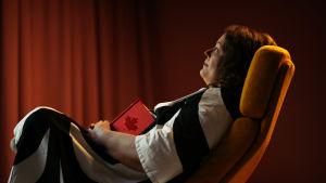 toimittaja Tina Caven kuvattuna sivulta, istuu tuolissa