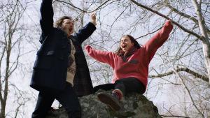 Gösta (Vilhelm Blomgren) och flickvännen Melissa (Amy Deasismont) står på en sten och hurrar.