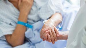 Patient och skötare håller hand.