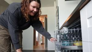Anna Teikari öppnar diskmaskinen i sin lägenhet och ser om glasen är rena.