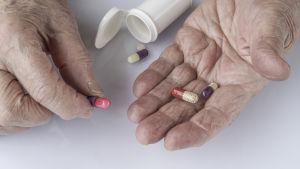 En äldre person håller i tabletter med en läkemedelsburk framför sig.