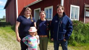 tre vuxna och en flicka på en gård