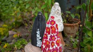 Tre små statyer i en trädgård, cirka 30 cm höga. Föreställer beduinkvinnor. Deras kläder är målade i vitt och svart förutom en som har målats i Marimekkos klassiska Unikko-mönster. Konstnären är Karin Björklund-Rissanen.