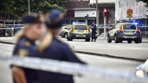 Svenska polisbilar och poliser vid en brottsplats.