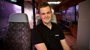 Jonathan sitter i bussen som han och hans vänner renoverat.
