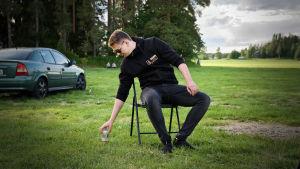 William sitter på en utvikbar stol på parkeringen utanför Klacken. Åkrar i bakgrunden.