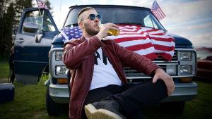 Hannes njuter av en öl framför sin Chevrolet med amerikanska flaggor i dörrarna och på motorhuven.