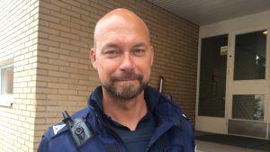 överkonstapel vesa hanski har full polisdräkt på i mörkblått och med olika polismärken på.