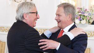 Jean-Claude Juncker och Sauli Niinistö ler glatt medan de omfamnar varandra.