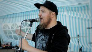 En man står och talar i en mikrofon.
