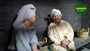 Tuija Pehkonen ja Anja Pohjola istuvan penkillä pyyhkeet päässään ja juttelevat.